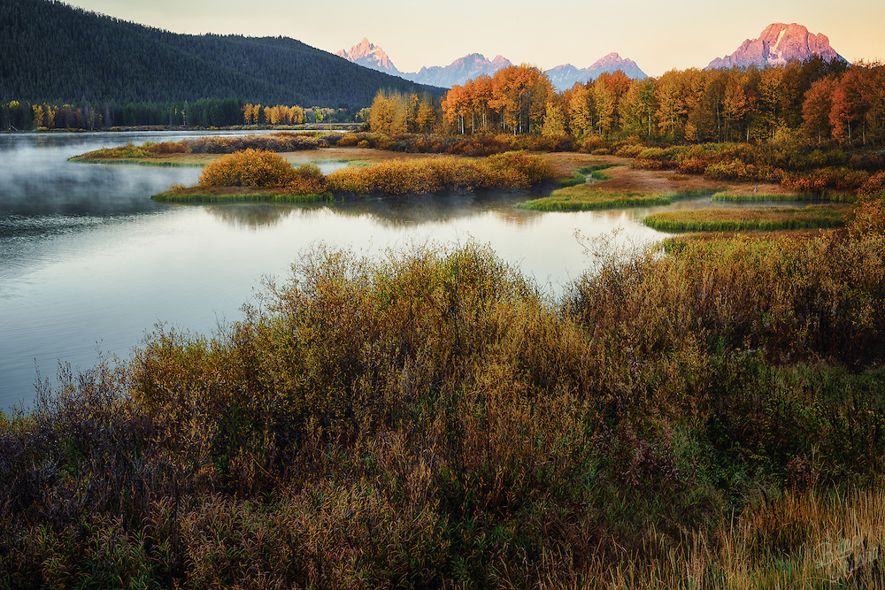 First light reaches over the horizon to touch the peaks of the Teton range bringing a warmth to the cool autumn air.