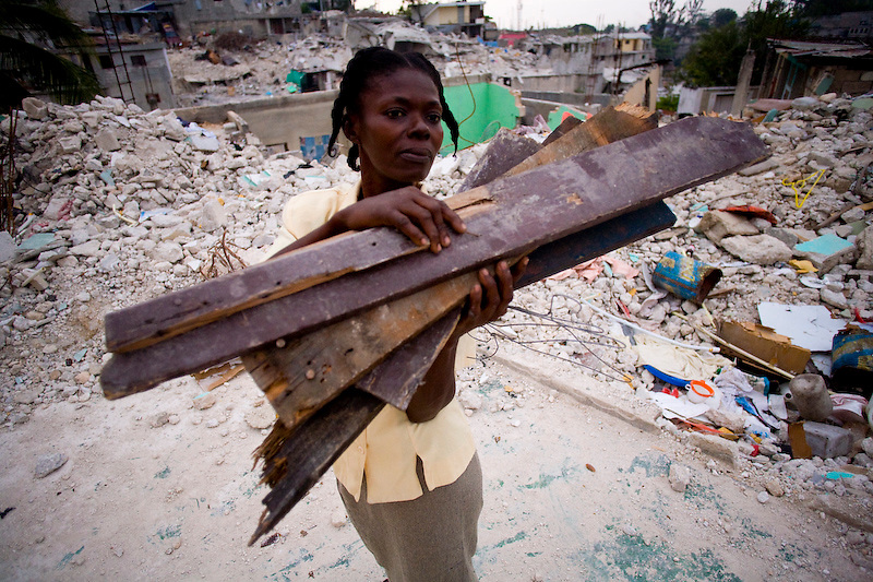 A woman collects wood scraps from her collapsed home to reinforce her termperary shelter. Petionville, Haiti. 3/17/2010. Photo by Ben Depp