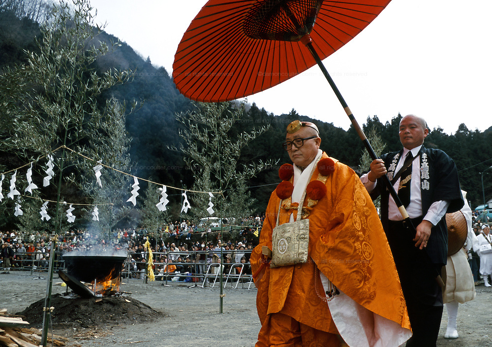 An Abbot Yamabushi or Mountain priest is escorted to his seat under a large red umbrella before the Hi Watari fire walking festival in Takao san Guchi, near Tokyo Japan. Sunday March 11th 2007