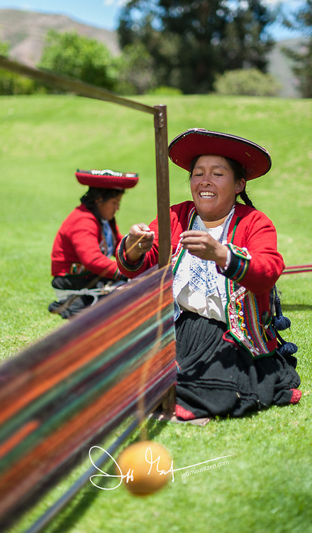 A Chinchero woman throws a ball of yarn while demonstrating traditional weaving techniques.