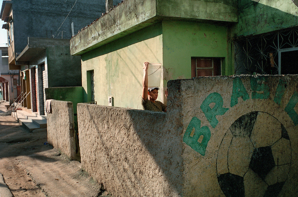 The absence of running water in houses in the favelas and the scarcity of sources where people can tap in to a clean supply of water mean that it is common for residents to have to walk some way to collect their water. Rio de Janerio, Brazil. 2001
