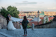 A young couple from Asia just married during a photo shoot at the Castle Stairs (Zamecke schody) which are leading from Prague Castle down to the Lesser Town (MalaStrana).