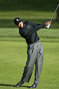 Professional golfer Tiger Woods smiles hits an iron shot in a round two match at the Accenture Match Play Championship World Golf Championships held at the La Costa Resort and Spa on February 27, 2004 in Carlsbad, California. ©Paul Anthony Spinelli