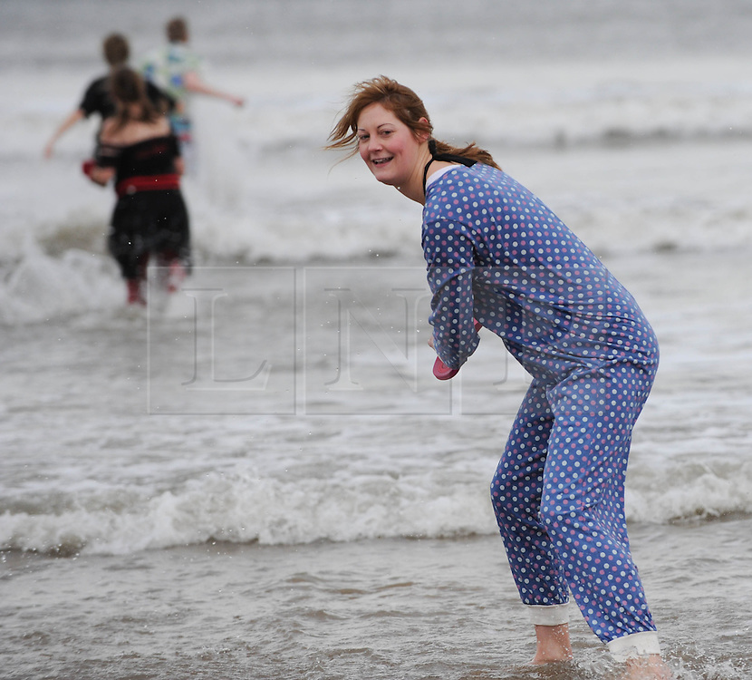 © Licensed to London News Pictures. 01/01/2014<br /> <br /> Saltburn, Cleveland, United Kingdom<br /> <br /> Swimmers brave the elements and the chilly north sea to take part in the annual New Year's Day dip on the beach in Saltburn, Cleveland to help raise money for the Saltburn Animal Rescue Association who offer care to injured or abandoned animals.<br /> <br /> Photo credit : Ian Forsyth/LNP