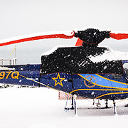 A Eurocopter A Star sits covered on a heli pad during a snow storm in Cordova, Alaska.