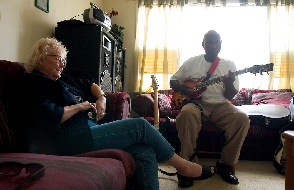 Carol Marble listens to David Lee Durham play in the living room of his house in Indianola, Miss., 2006.