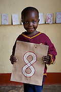 A young boy holds up a sign of his favourite number 8 during a class at  Miles2Smiles Welfare Centre in Kalerwe market, Kampala, Uganda. The centre is a day care and welfare service for market vendors with babies and infants aged 6 months to 5 years old.