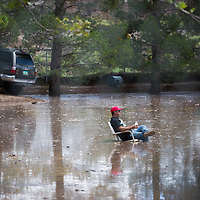Dough Bickel takes a short break while he helps his friend, Mark Sale, clean up flood water after Wednesday nights storms in Doña Ana. Thursday Aug. 24, 2017.