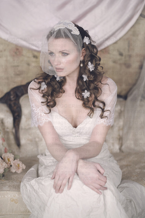 A pretty young regency bride in her early 20s  sits in a fancy room with a veil over her face, looking a little sad