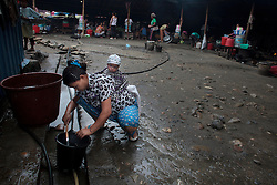 A Kachin woman fill a water bucket in a Internal Displacement People refugee camp in Laiza village close to the China border, Myanmar on July 13, 2012. According to KIO (Kachin Independence Organization) sources around 50000 Kachin people live as refugees in those camps.