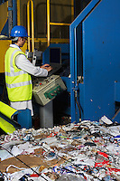 Man operating conveyor belt in recycling factory side view