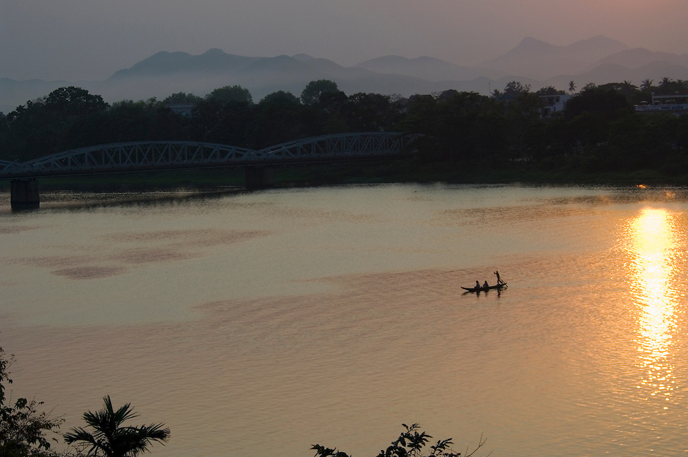 Vietnam: Hue<br /> A boatwoman ferries two passengers back across the Perfume River at sunset. The mountains of Laos are in the distance.
