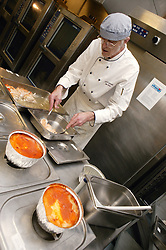 Hospital Chef transferring cooked food into gastronome containers to be transferred to ward trolleys,
