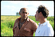 Monsanto agronomst, Victor Carrao, talks with sharecropper Luis Acosta at Granja Bretanhas farm. Brazil
