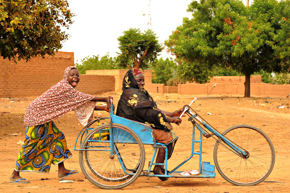 "KIOTA, NIGER  13-04-20   - Jamila Amadou, who has untreated club feet, gets a push through the sand from a young woman in Kiota, Niger, on April 20 2013. Jamila, who is currently unemployed, is hoping to be the recipient of a survival yard. ""It will reduce my suffering and provide me with some income.""   Photo by Daniel Hayduk"