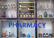 Mortars and pestles and old bottles are being displayed in a pharmacy display window on 10th Avenue in Manhattan, New York City