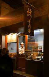 A toque-topped vendor awaits visitors at his food shop, night market, Beijing, China.