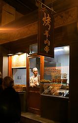 A toque-topped vendor awaits visitors at his food shop, night market, Beijing, China.