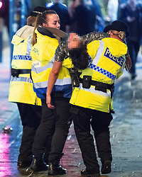 **2018 Pictures of the year by London News Pictures**<br /> © Licensed to London News Pictures . 01/01/2018. Manchester, UK. Police and a welfare support worker lift a woman off the ground and carry her away from the Printworks . Revellers celebrate the start of the New Year in Manchester City Centre . Photo credit: Joel Goodman/LNP