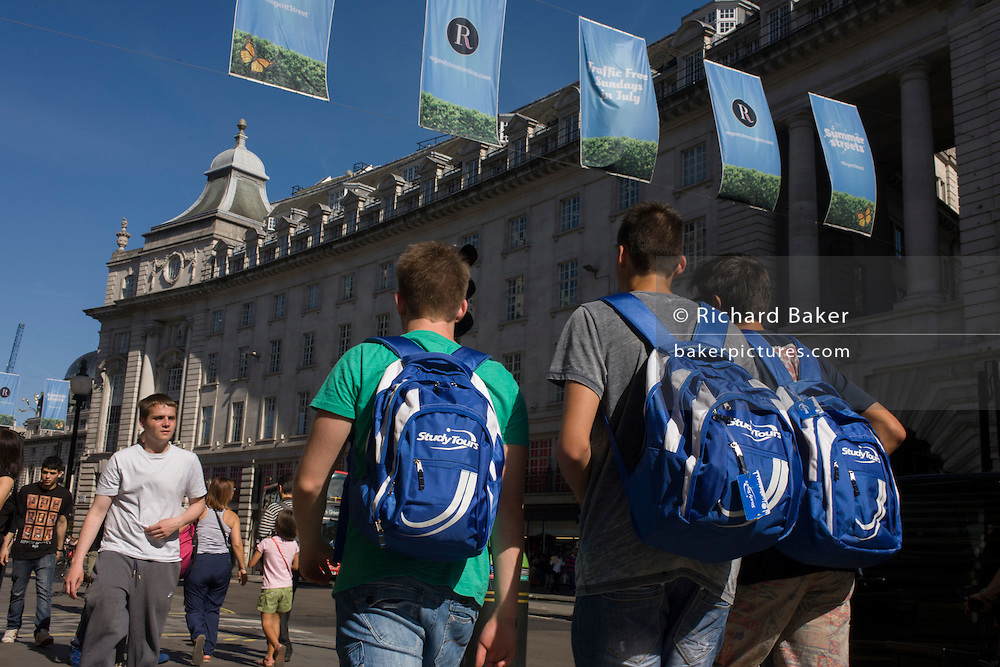 Three young tourists boys carry identical tour rucksacks beneath blue banners across Regent Street, central London.