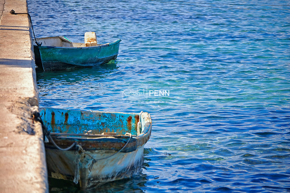 Two Bahamian made wooden boats tied on the dock during low tide in Nassau Harbour