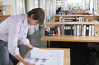 Man studying blueprint in office