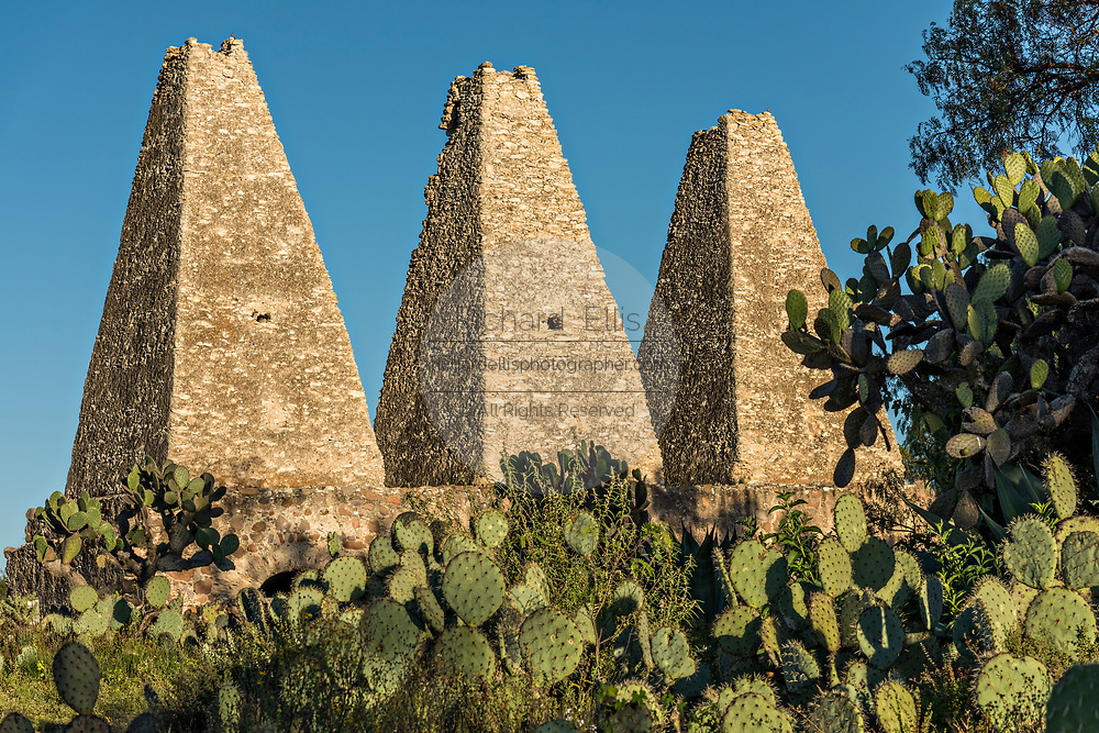 The cone shaped smelting towers of the shuttered mine of the Santa Brigida Hacienda in the ghost town of Mineral de Pozos, Guanajuato, Mexico. The town, once a major silver mining center was abandoned and left to ruin but has slowly comeback to life as a bohemian arts community.