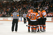 RIT players celebrate a goal by Michael Holland (left) during a game against Brock University at the Gene Polisseni Center on Saturday, October 4, 2014.