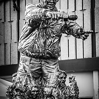 "Harry Caray statue at Wrigley Field in black and white. Harry Caray was a very popular announcer for the Chicago Cubs and is known for leading fans in singing ""Take Me Out to the Ball Game"" during the seventh inning stretch."