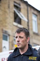 © Licensed to London News Pictures. 08/07/2015. Barnsley, UK. Picture shows Andy Strelczenie investigator for the South Yorkshire Fire & Rescue service speaking to Media. Two people have died in a house fire on Cherry Tree Street in Elscar, Barnsley. A man & woman were pronounced dead after the blaze at about 18:50 on Tuesday. A South Yorkshire Fire & Rescue spokesman said despite the considerable efforts of firefighters & ambulance crews at the scene, both sale passed away. Photo credit : Andrew McCaren/LNP