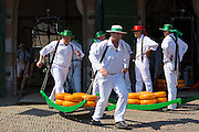Porters / carriers carrying wheels / rounds of Gouda cheese by stretcher from weigh house at Alkmaar cheese market, The Netherlands