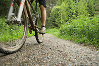 Cyclist on track in countryside low section
