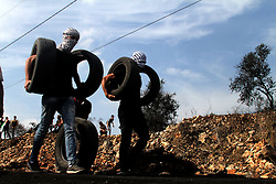 November 11, 2016 - Nablus, West Bank, Palestine - A Palestinian protester throws a tire on a fire during clashes with Israeli security forces following a demonstration against the expropriation of Palestinian land by Israel on November 11, 2016 in the village of Kfar Qaddum, near Nablus, in the occupied West Bank. (Credit Image: © Moahmmed Turabi/ImagesLive via ZUMA Wire)