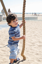little boy playing on a rope at the beach in Santa Monica, CA