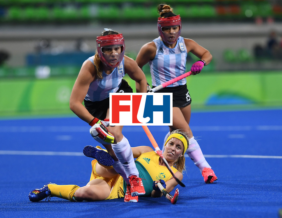 Australia's Emily Smith (C) falls as Argentina's Julia Gomes (L) and Argentina's Maria Granatto run past during the women's field hockey Australia vs Argentina match of the Rio 2016 Olympics Games at the Olympic Hockey Centre in Rio de Janeiro on August, 11 2016. / AFP / MANAN VATSYAYANA        (Photo credit should read MANAN VATSYAYANA/AFP/Getty Images)