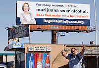 A man who identified himself as a medical marijuana patient poses with a new billboard erected on top of a liquor store in Denver April 6, 2012.  Colorado voters are set in November to decide whether to defy the federal government and legalize marijuana for recreational use under state law.  REUTERS/Rick Wilking (UNITED STATES)