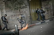 An Israeli soldier puts out a fired bottle during clashes in the centre of the West Bank city of Hebron February 12, 2010. Palestinians clashed with Israeli troops in Hebron amid outrage over Israel's plan to restore two flashpoint Jewish holy sites in the occupied territory.