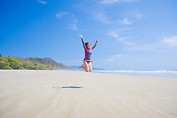 Woman jumping at Playa Hermosa in Costa Rica