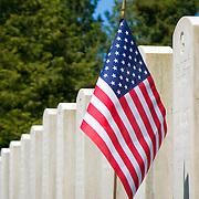 A single US Flag stands by a headstone at the Veterans Memorial Cemetery, Evergreen-Washelli cemetery, Seattle, Washington