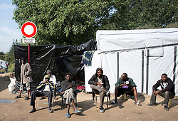 © Licensed to London News Pictures. 30/08/2015. Calais, France. A group of men from Sudan gather together in chairs at Salam, by the refugee camp in Calais, also known as the Jungle. Tomorrow the French PM, Manuel Valls, will visit the day centre Jules Ferry at the camp. Photo credit : Isabel Infantes/LNP