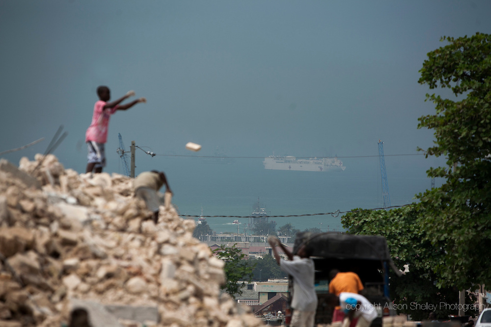 Men clear debris from the site of the collapsed Notre dame du Perpetuel Secous Catholic church in the Bel Air neighborhood of Port-au-Prince, Haiti, Friday, February 27, 2010.  In the harbor is the U.S. hospital ship, the U.S.N.S. Comfort.