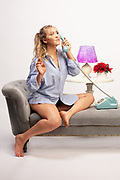Beautiful blond model Brenna Smith wearing a ponytail in in a boyfriend dress shirt sitting on a chaise while talking on a retro dial phone