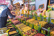 Shopkeeper selling green and black olives on sale at food market in Kadikoy district, Asian side of Istanbul, East Turkey