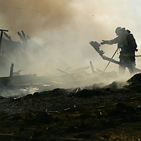 Crystal Chatham The Desert Sun<br /> <br /> 1/15/2008 -- Fire crews work through debris in an outbuilding on Saturday, November 15 during a structure fire at Monroe and Avenue 54 in La Quinta. The fire destroyed an abandoned single family dwelling and two outbuildings; a third outbuilding was spared. Eight engines, one water tender, a truck company, and one breathing support unit responded to the blaze which spread from the home to palm trees and surrounding vegetation before engulfing the outbuildings. Crews from Indio, Coachella, La Quinta, and Thermal responded to the 9:25 a.m. call.