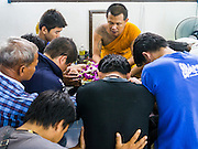"22 MARCH 2013 - NAKHON CHAI SI, NAKHON PATHOM, THAILAND: Men pray and make offerings to a make after receiving sacred Sak Yant tattoos at Wat Bang Phra during the annual tattoo festival. Wat Bang Phra is the best known ""Sak Yant"" tattoo temple in Thailand. It's located in Nakhon Pathom province, about 40 miles from Bangkok. The tattoos are given with hollow stainless steel needles and are thought to possess magical powers of protection. The tattoos, which are given by Buddhist monks, are popular with soldiers, policeman and gangsters, people who generally live in harm's way. The tattoo must be activated to remain powerful and the annual Wai Khru Ceremony (tattoo festival) at the temple draws thousands of devotees who come to the temple to activate or renew the tattoos. People go into trance like states and then assume the personality of their tattoo, so people with tiger tattoos assume the personality of a tiger, people with monkey tattoos take on the personality of a monkey and so on. In recent years the tattoo festival has become popular with tourists who make the trip to Nakorn Pathom province to see a side of ""exotic"" Thailand. The 2013 tattoo festival was on March 23.   PHOTO BY JACK KURTZ"