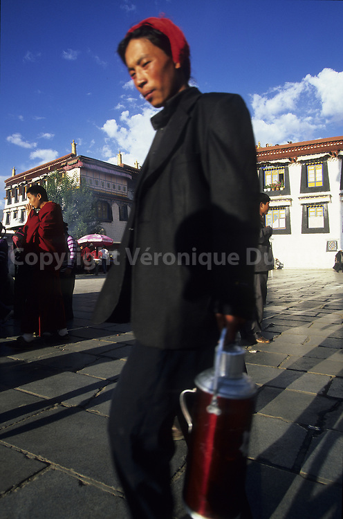 TIBETAN PILGRIM WITH HIS THERMOS FLASK AT JOKHANG SQUARE, LHASA, TIBET