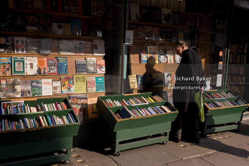 Browsing man outside traditional, but disappearing, bookshop on Charis Cross Road.