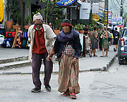 An old man with sunglasses and woman walk together down the street of Lakeside, in Pokhara, Nepal.
