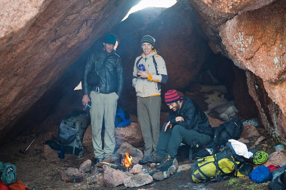Obadiah Reid (l-r), David Coffey, and Marco Binotti camp in a cave in McMurdy Park, Lost Creek Wilderness, Colorado.