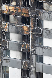 © Licensed to London News Pictures. 18/06/2017. London, UK. Burnt exterior panels are seen on Grenfell tower block. The blaze engulfed the 27-storey building killing dozens - with 34 people still in hospital, many of whom are in critical condition. The fire brigade say that they don't expect to find anyone else alive. Photo credit: Peter Macdiarmid/LNP